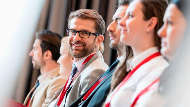 Man som ler och kollar in i kamera på föreläsning – Nacka företagarträff